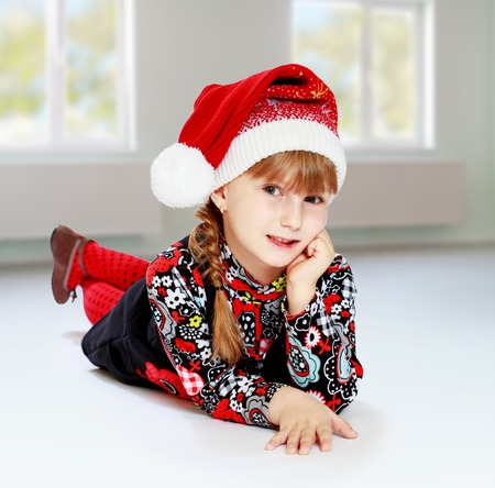 Little girl in santa claus hat ale a lesson. Happiness, winter holidays, new year, and childhood. photo