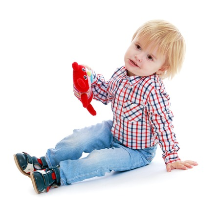 babyroom: Little boy sitting on the floor teddy bear .Childhood education development in the Montessori school concept. Isolated on white .