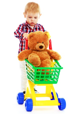 Little boy riding in the truck of a teddy bear.Early years learning a happy childhood concept.Isolated on white . photo