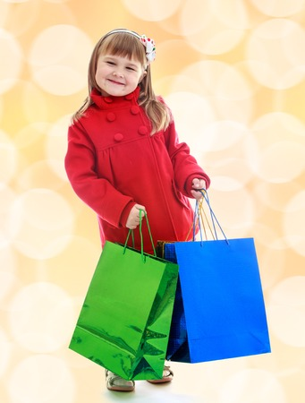 charming: Charming little girl goes shopping with large multi-colored packages.