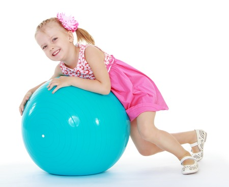 Girl in pink dress lies on a large exercise ball.Very cheerful little girl. photo