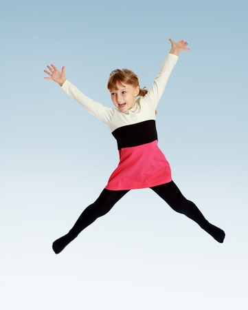 6 7 years: Cheerful girl jumping high up raised arms wide. Stock Photo