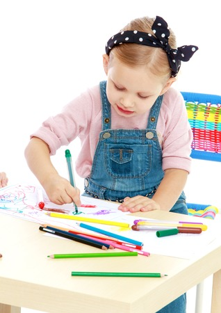 practice primary: Charming little girl draws with markers while sitting at table.Childhood education development in the Montessori school concept. Isolated on white background.