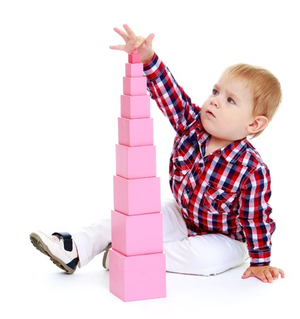 Little boy puts cubes.Early years learning a happy childhood concept.Isolated on white background.