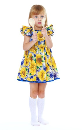 petti: Cute little girl colorful dress holding a wooden spoon. Stock Photo