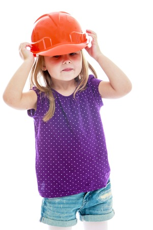 make belief: Curious little girl in the construction helmet.Happy childhood, fashion, autumnal mood concept. Isolated on white background Stock Photo