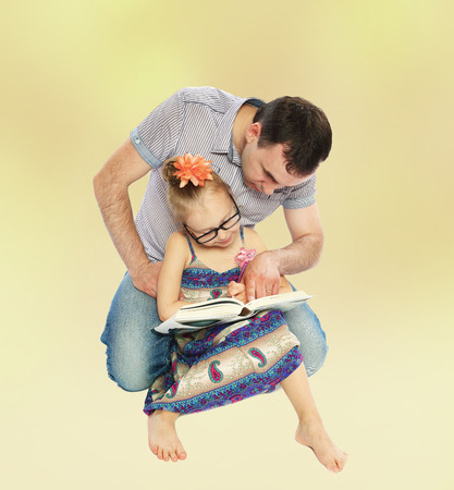 6 7 years: Positive young dad reading a book with her daughter.
