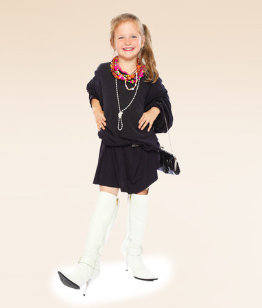 Fashionable little girl in a black dress and long boots on high sole.