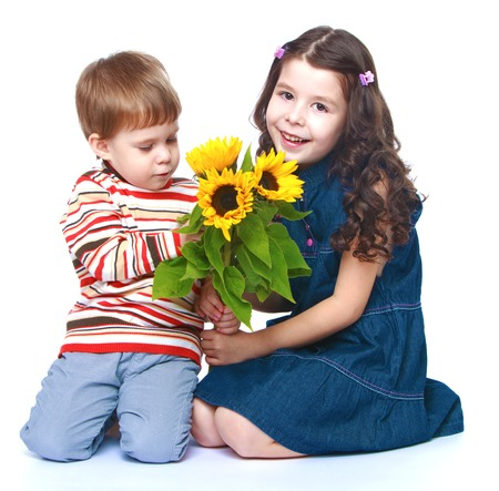 little brother with her older sister sitting on the floor and holding a bouquet of yellow flowers.Isolated on white background. photo