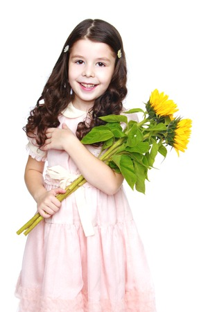 Smiling little girl in a pink dress holding a bouquet of yellow flowers.Isolated on white background. photo