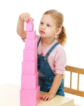 小さな女の子はピンクのピラミッドを収集します。モンテッソーリ学校概念の幼年期の教育の開発。白い背景で隔離されました。