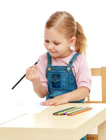 Little girl draws pencils sitting at the table.Childhood education development in the Montessori school concept. Isolated on white background. photo
