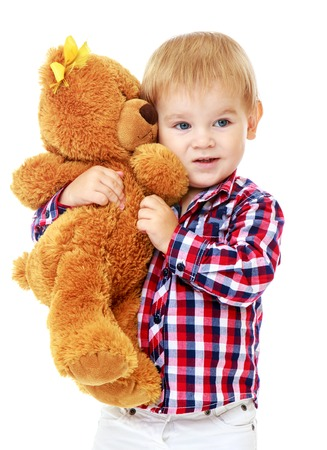 Little boy is playing in the kindergarten with a teddy bear.Early years learning a happy childhood concept.Isolated on white background. photo