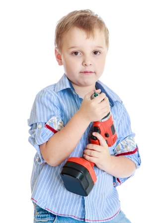Apprenticeships, child labor, the joy of technical knowledge concept.Little boy where in the hands of an electric screwdriver.