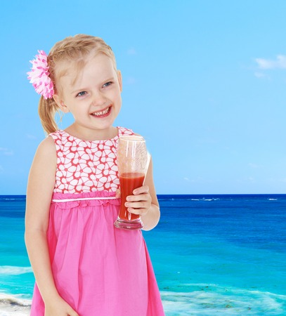 6 7 years: Smiling little girl with a glass of juice on a sea background.
