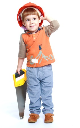 Little boy in the construction helmet ankle boots in hand saw.Isolated on white background. photo
