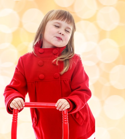 Cute little girl holding a red pen from the cart. Happiness, winter holidays, new year, and childhood. photo