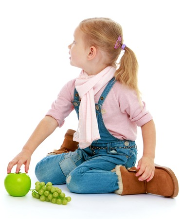Little girl sitting on the floor and holding a hand an apple.Childhood education development in the Montessori school concept. Isolated on white background. photo