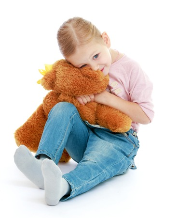 Little girl hugging a teddy bear.Childhood education development in the Montessori school concept. Isolated on white background. photo