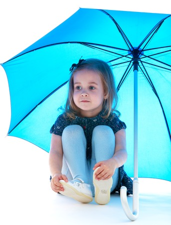 russian ethnicity caucasian: Little girl sitting on the floor sheltered umbrella.Isolated on white background. Stock Photo