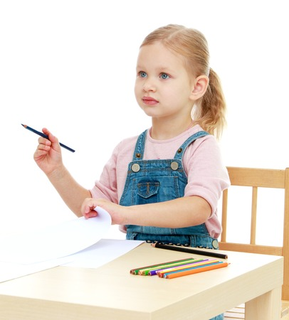 Little girl draws pencils sitting at the table Isolated on white background. photo