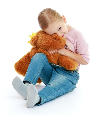 Little girl hugging a teddy bear Isolated on white background. photo