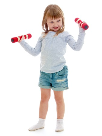 Little girl in sportswear holding a dumbbell. Happy childhood, fashion, autumnal mood concept. Isolated on white background photo