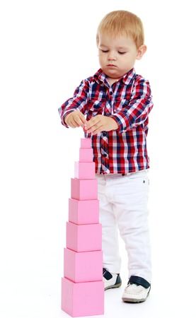 Little boy builds a pyramid in the Montessori school.Early years learning a happy childhood concept.Isolated on white background. photo