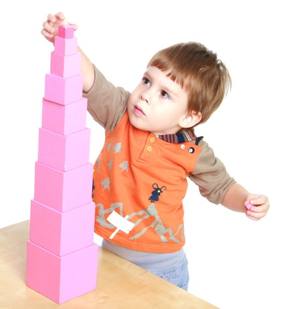 montessori: Little boy builds Red Pyramid in the Montessori classroom.Isolated on white background.