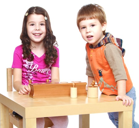 montessori: brother and sister sitting at the table and play in a Montessori classroom.Isolated on white background.