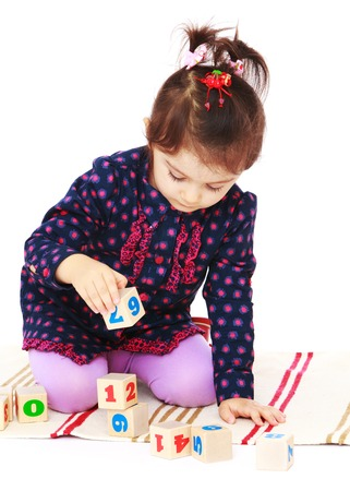montessori: Little girl plays cubes sitting on the floor. In the Montessori classroom .Isolated on white background. Stock Photo