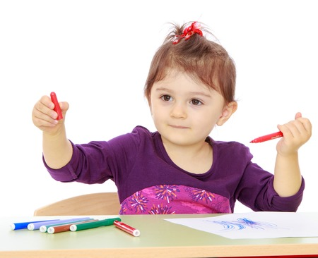 montessori: Little girl with enthusiasm draws colored markers while sitting at the table. Montessori School.Isolated on white background. Stock Photo