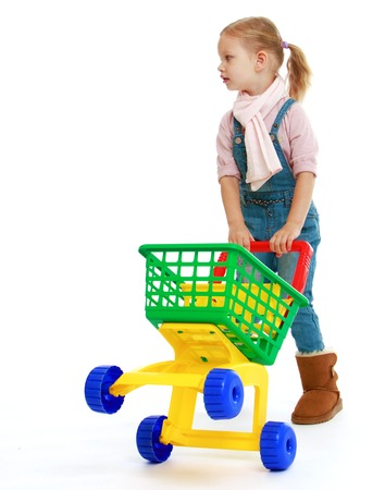 Charming little girl with a toy truck.Childhood education development in the Montessori school concept. Isolated on white background. photo