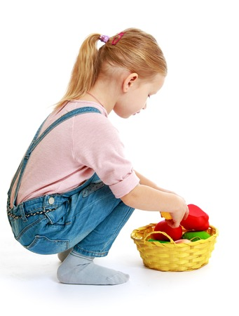 Girl considers lying in a basket of fruit.Childhood education development in the Montessori school concept. Isolated on white background. photo