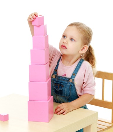 preschool: Little girl collects the pink pyramid.Childhood education development in the Montessori school concept. Isolated on white background.