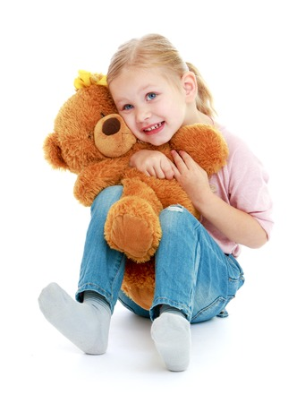 montessori: Little girl hugging a teddy bear.Childhood education development in the Montessori school concept. Isolated on white background. Stock Photo