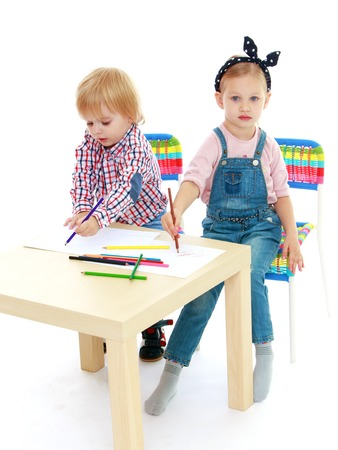 practice primary: Girl and boy sitting at the table draw.Childhood education development in the Montessori school concept. Isolated on white background.