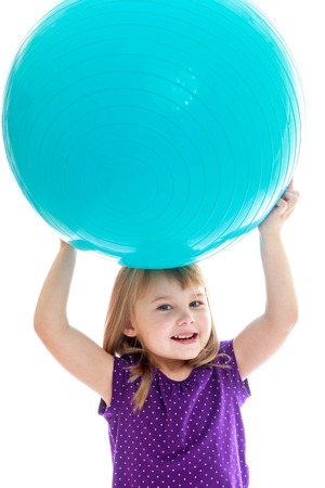 Cheerful little girl is holding her head on a large sports ball. Happy childhood, fashion, autumnal mood concept. Isolated on white background photo