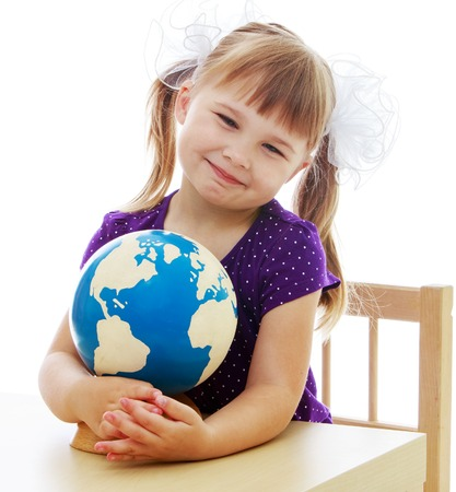 baby 4 5 years: Happy childhood, adolescence, the development of the family concept. Little girl examines the globe isolated on white background. Stock Photo