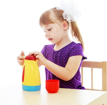baby 4 5 years: Happy childhood, adolescence, the development of the family concept.Little girl sitting at the table pouring from a plastic tea kettle. Isolated on white background.