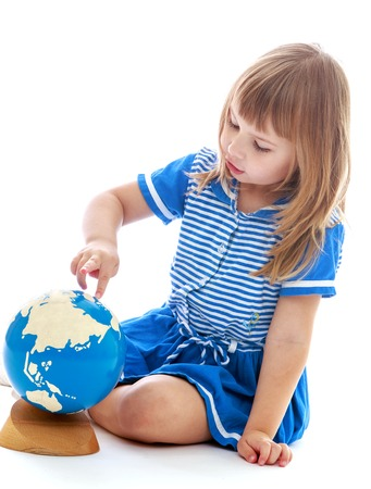 baby 4 5 years: Little curious girl examines the globe sitting on the floor isolated on white background.Happy childhood, adolescence, the development of the family concept. Stock Photo