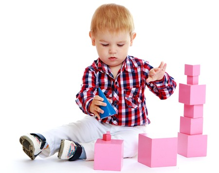 Little boy playing with pink cubes.White background, isolated photo.