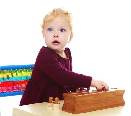 montessori: very smart little girl is developing Montessori material.White background, isolated photo.