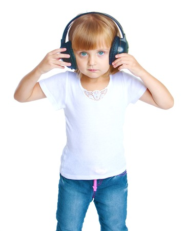 pre adolescent child: Little girl listening to music on headphones.Isolated on white background. Stock Photo