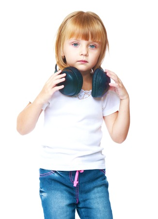 Little girl listening to music on headphones.Isolated on white background. Stock Photo