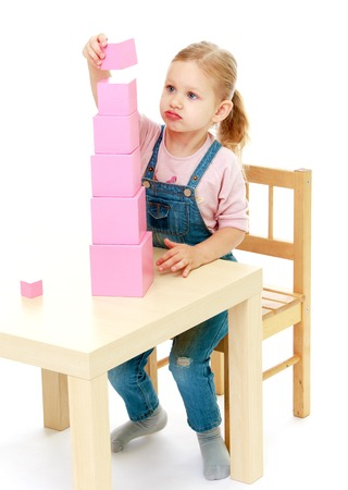 montessori: Little girl collects the pink pyramid.Childhood education development in the Montessori school concept. Isolated on white background.