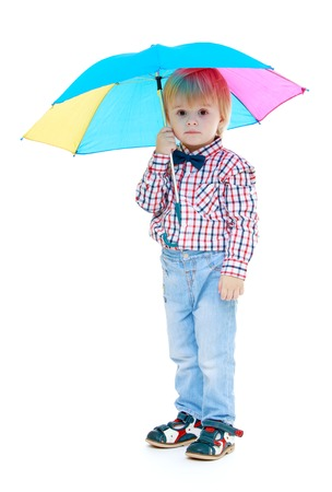 Little boy stands under a colorful umbrella.Childhood education development in the Montessori school concept. Isolated on white background. photo