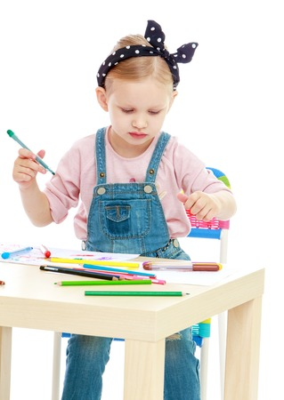 Charming little girl draws with markers while sitting at table.Childhood education development in the Montessori school concept. Isolated on white background. photo