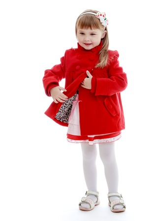 very fashionable little girl unzips a beautiful red coat. photo