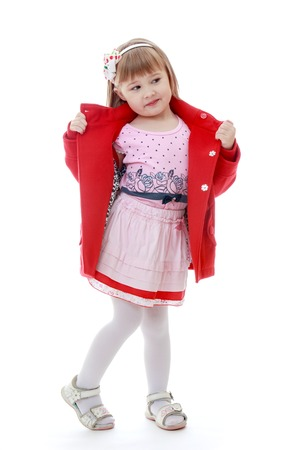 Fashionable little girl bright red coat in a beautiful pink dress. Happy childhood, fashion, autumnal mood concept. Isolated on white background photo